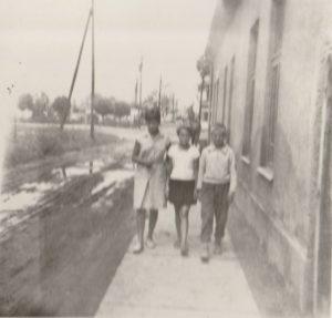 A fényképen lévő alakok az a ház mellett sétálnak el, amely Füster Gyula tulajdonában állt a II. világháború előtt, a Rózsa Ferenc, avagy korábbi nevén Vasút utcában. Ebben a házban működött anno a Gitta – fodrászat.   A fotó az 1960-as évekre datálható.