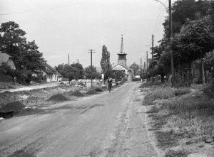 A fotón a régi Posta utca látszik, amely valamikor a Szöllősy Móricz utcanevet viselte. A kép bal szélén az egykori ruházati és vasbolt épületének egy részlete vehető ki, mellette a nagyhíd és a gárdonyi katolikus templom.
