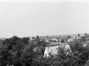 A fénykép a református templom tornyából készült az 1960-as években. A kép, apró részletében látható Hragyil János egykori fodrász üzlete.